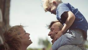 Padres jovenes con su hijo adorable que besa y que se divierte en patio almacen de metraje de vídeo