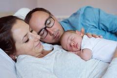 Padres jovenes con su hijo recién nacido del bebé que miente en cama imagenes de archivo