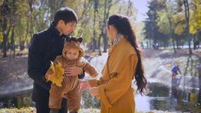 Padres jovenes con un niño en el bosque que hace una pausa la charca almacen de metraje de vídeo