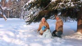 Padres jovenes con un niño que juega en un invierno metrajes