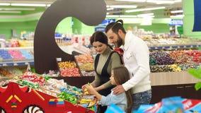Padres jovenes con una pequeña hija elegir los chocolates dulces en un supermercado almacen de metraje de vídeo