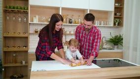 Padres jovenes e hija del niño que se divierte junta que rueda la pasta en cocina almacen de metraje de vídeo
