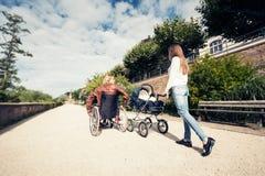 Padres jovenes en silla de ruedas con el cochecito de bebé en el parque fotografía de archivo