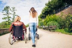 Padres jovenes en silla de ruedas con el cochecito de bebé en el parque imagen de archivo