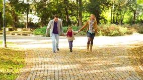 Padres jovenes felices con la hija en parque metrajes
