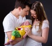 Padres jovenes felices y muchacha recién nacida foto de archivo