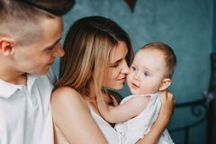 Padres jovenes que abrazan y que besan a la pequeña hija imagen de archivo libre de regalías