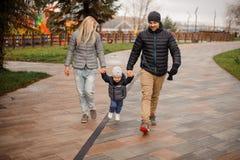 Padres jovenes que caminan abajo de la calle con un pequeño hijo Imagenes de archivo