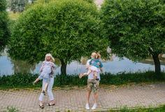 Padres jovenes que dan vuelta alrededor, girando con los niños en el parque foto de archivo