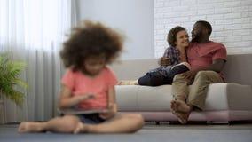 Padres jovenes que disfrutan del pasatiempo común que mira a su hija el jugar en la tableta fotografía de archivo libre de regalías