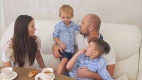 Padres jovenes que intentan conseguir a su pequeño hijo obstinado comer imagenes de archivo