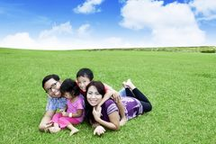 Padres jovenes que juegan con sus niños en parque Fotografía de archivo libre de regalías