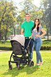 Padres jovenes que presentan con su bebé en un parque Imagen de archivo