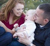 Padres jovenes que ríen con el muchacho del niño en parque Imagenes de archivo