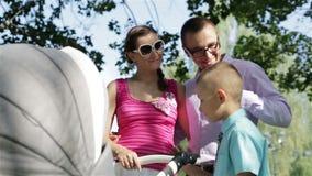 Padres jovenes que se colocan cerca de un cochecito de niño en un parque metrajes