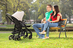 Padres jovenes que se sientan con su bebé en parque Fotos de archivo