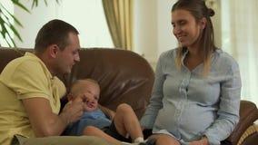 Padres jovenes y poco hijo en el sofá junto almacen de video