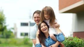 Padres jovenes y su pequeña hija El padre abraza a sus muchachas Idilio de la familia almacen de video