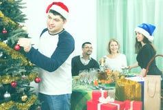 Padres maduros con los niños adultos que se preparan para la Navidad Imagen de archivo libre de regalías
