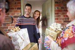 Padres mayores que son saludados por el descendiente adulto como llegan para la visita el día de la Navidad imágenes de archivo libres de regalías