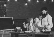 Padres orgullosos que miran éxito de los hijos Concepto de la ayuda del padre Padres que miran su dibujo del hijo, aprendiendo es imagen de archivo