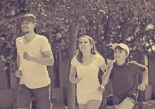 Padres positivos con el hijo que corre en parque Fotos de archivo libres de regalías