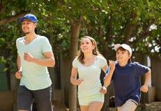 Padres positivos con el hijo que corre en parque Fotografía de archivo libre de regalías