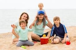 Padres positivos con los niños que se sientan en la playa arenosa Imagenes de archivo