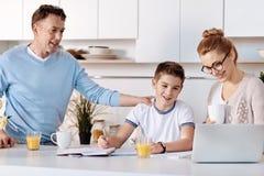 Padres positivos que ayudan a su hijo con la asignación casera Imagen de archivo