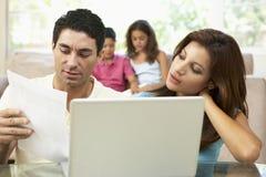 Padres preocupantes que usan la computadora portátil en el país Imagenes de archivo