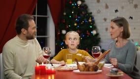 Padres que abrazan a la hija en el almuerzo de Navidad, familia feliz que celebra víspera del día de fiesta almacen de metraje de vídeo