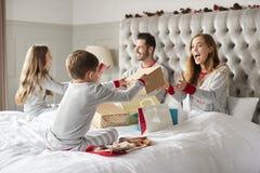 Padres que abren los regalos de niños como ellos Sit On Bed Exchanging Present el día de la Navidad imagen de archivo libre de regalías