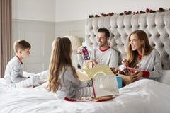 Padres que abren los regalos de niños como ellos Sit On Bed Exchanging Present el día de la Navidad fotos de archivo libres de regalías
