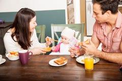 Padres que alimentan a su bebé en casa Fotos de archivo libres de regalías