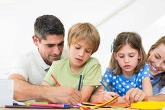 Padres que ayudan a niños en el colorante fotografía de archivo