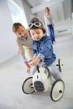 Padres que ayudan a su coche del juguete del montar a caballo del niño pequeño Imagenes de archivo