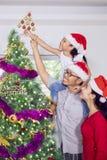 Padres que ayudan a su hija cerca de un árbol de navidad Foto de archivo libre de regalías