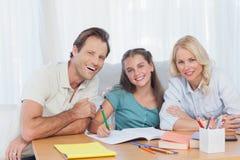 Padres que ayudan a su hija a hacer su preparación Imagen de archivo libre de regalías