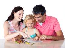 Padres que ayudan a su hija que hace la preparación Fotos de archivo libres de regalías