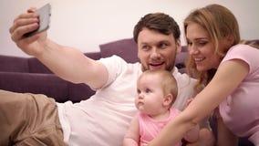 Padres que besan al bebé Familia feliz que toma la foto del selfie en casa almacen de video