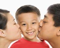 Padres que besan al hijo.