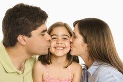 Padres que besan a la hija. Imagen de archivo
