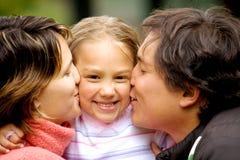 Padres que besan a la hija Imagen de archivo libre de regalías