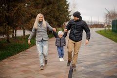 Padres que caminan abajo de la calle y que se divierten con un pequeño hijo Imagen de archivo