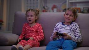 Padres que cogen a los niños que juegan al juego en la noche, control de la disciplina, comportamiento metrajes