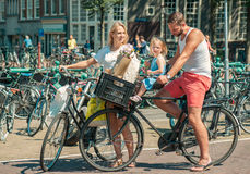 Padres que completan un ciclo en las calles de Amsterdam Imágenes de archivo libres de regalías