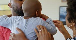 Padres que consuelan a su hijo en casa 4k almacen de metraje de vídeo