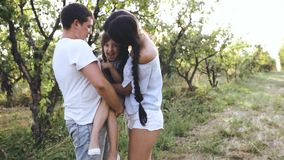 Padres que cosquillean a la muchacha de risa en naturaleza almacen de metraje de vídeo