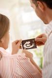 Padres que cuentan con al bebé Imagen de archivo libre de regalías