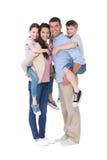 Padres que dan a cuestas paseo a los niños sobre el fondo blanco Fotografía de archivo